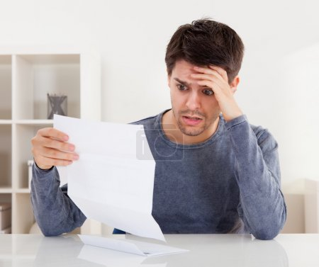 Horrified man reading a document