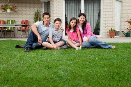 Photo pour Portrait de famille caucasien assis devant leur maison en souriant - image libre de droit