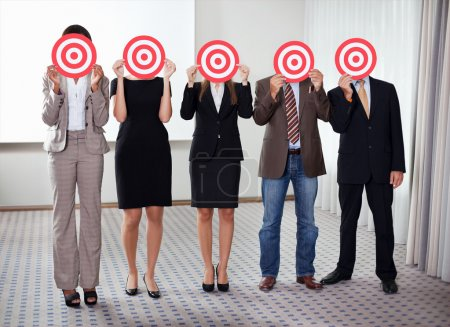 Photo for Group of business holding a target against their faces - Royalty Free Image