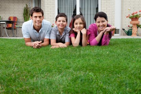 Photo for Portrait of happy young family lying on grass outside their house - Royalty Free Image