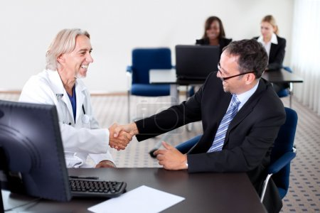 Doctor shaking hands with a patient at a desk