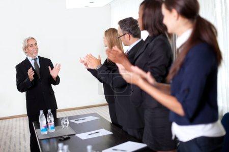 Photo pour Collègues pour féliciter un homme d'affaires au cours d'une réunion d'affaires - image libre de droit