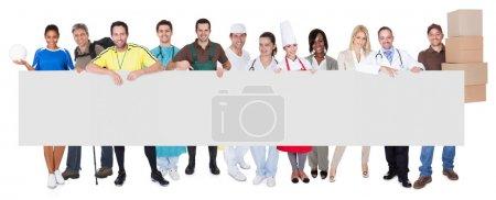 Photo pour Groupe de professionnels divers présentant bannière vide. Isolé sur blanc - image libre de droit