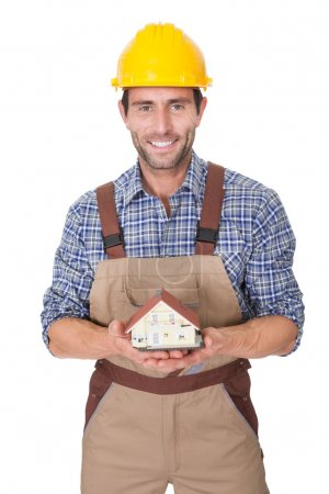 Construction worker presenting house model