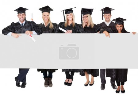 Photo for Group of graduate students presenting empty banner. Isolated on white - Royalty Free Image