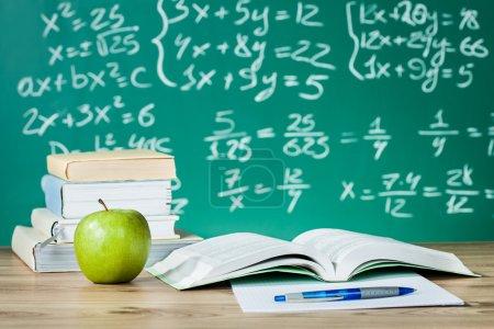 Photo pour Manuels scolaires sur un bureau devant le tableau noir - image libre de droit