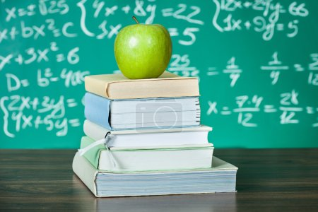 Photo for Stack of school textbooks and apple in front of blackboard - Royalty Free Image