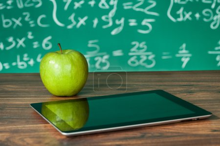 Photo for Digital tablet and apple on the desk in front of blackboard - Royalty Free Image