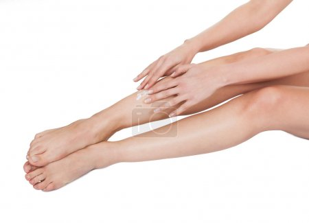 Woman Applying Cream To Her Legs