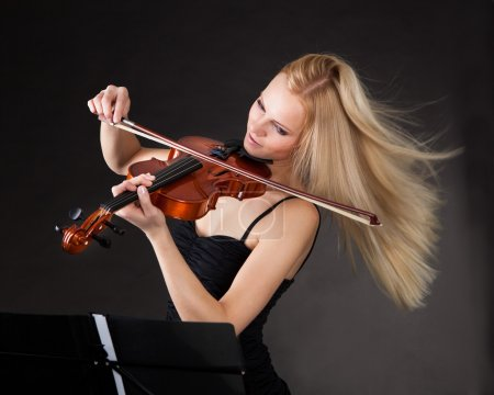 Photo for Young woman passionately playing violin over black background - Royalty Free Image