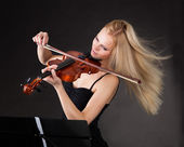 Young woman passionately playing violin