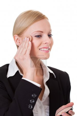 Attractive businesswoman applying foundation