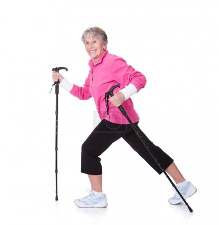 Foto de Mujer mayor caminando con postes de senderismo en fondos blancos - Imagen libre de derechos