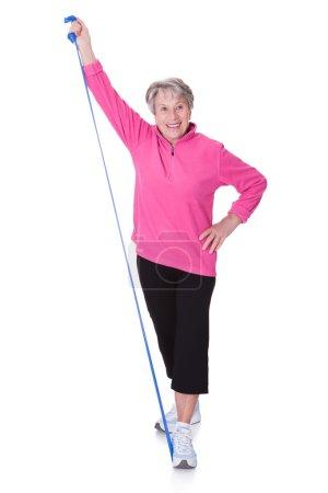 Photo pour Femme aînée étirant l'équipement d'exercice sur fond blanc - image libre de droit