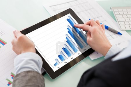 Businessperson Analyzing Graph On Digital Tablet I...