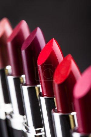 Photo pour Rouge à lèvres dans une rangée isolé sur fond gris - image libre de droit