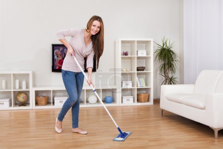 Photo for Portrait Of Young Woman Mopping Floor At Home - Royalty Free Image