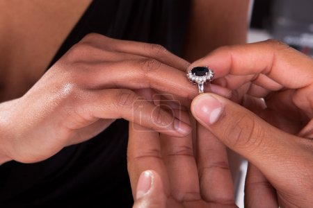 Photo pour Gros plan de la main masculine insérant une bague de fiançailles dans un doigt - image libre de droit