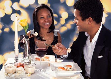 Photo pour Portrait de couple romantique, manger des sushis au dîner - image libre de droit