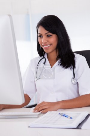 Happy Female Doctor Using Computer