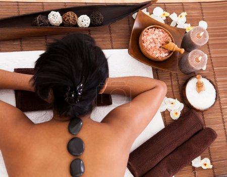 Photo pour Jeune femme obtenir un traitement spa avec massage pierre - image libre de droit
