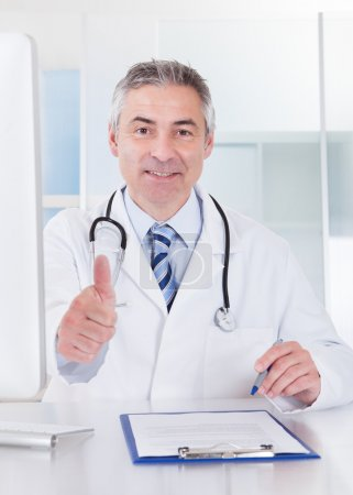 Mature Male Doctor Showing Thumbs Up Sign