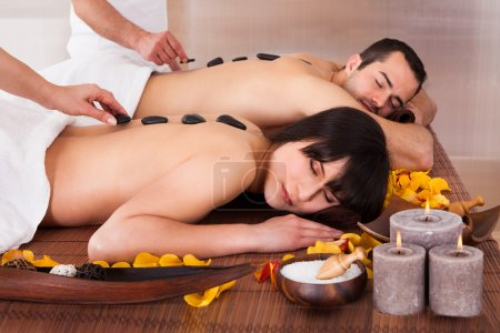 Beautiful Young Couple Enjoying Hot Stone Therapy