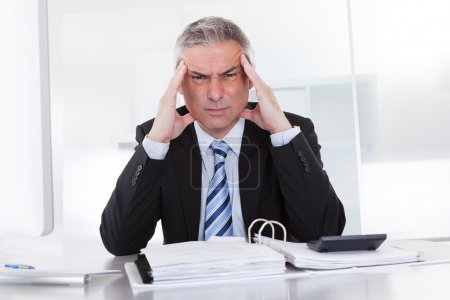 Photo for Mature Businessman Suffering From Head Ache At Work - Royalty Free Image