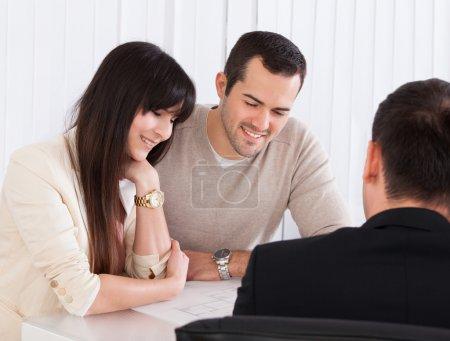 Photo pour Heureux jeune couple discuter avec l'expert-conseil au bureau - image libre de droit