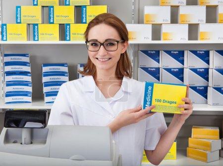 Female Pharmacist Showing Drug In Pharmacy