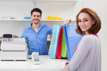 Cashier Handing Over Shopping Bag To Customer