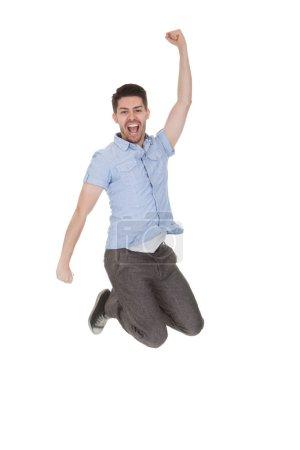 Photo pour Jeune homme sautant avec les bras levés sur fond blanc - image libre de droit