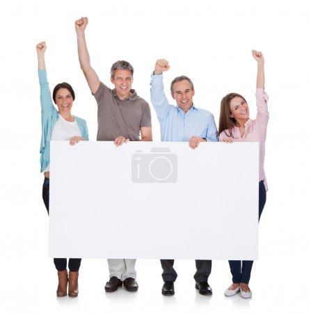 Photo pour Groupe de personnes heureuses tenant la plaque sur fond blanc - image libre de droit
