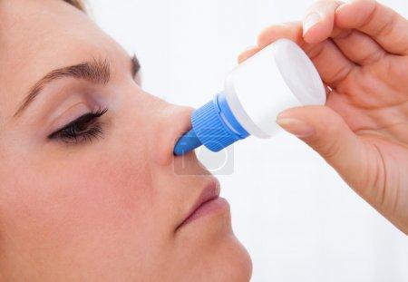 Photo pour Gros plan d'une femme utilisant un spray nasal isolé sur fond blanc - image libre de droit