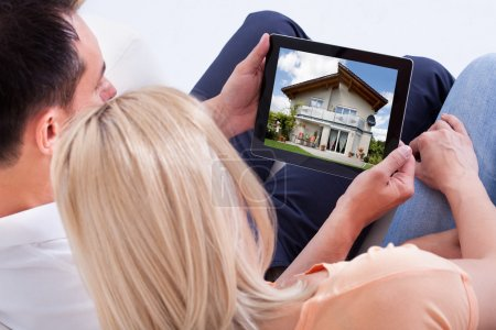 Photo for Couple Looking At House On Digital Tablet's Screen - Royalty Free Image