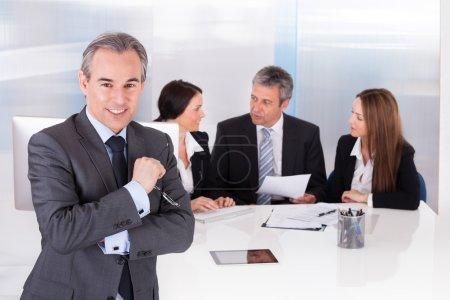 Photo pour Heureux homme d'affaires, debout devant ses collègues de bureau - image libre de droit