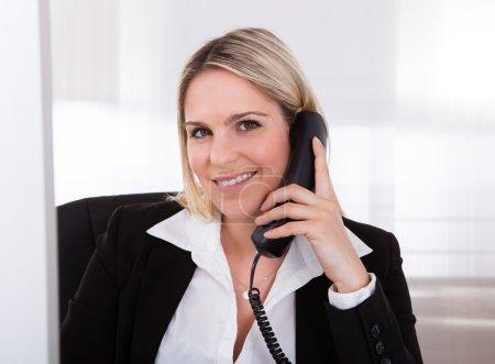 Happy businesswoman talking on telephone