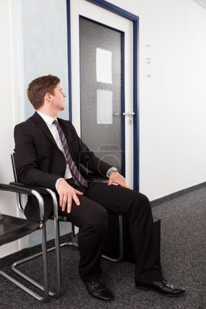 Photo for Anxious man waiting for job interview sitting on chair - Royalty Free Image