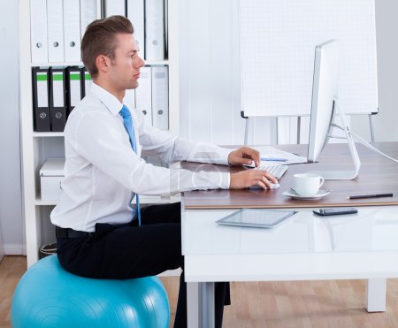 Businessman Sitting On Pilates Ball And Using Computer