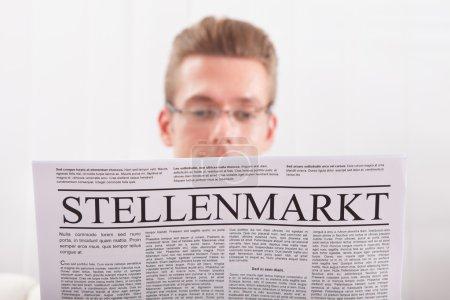 Photo pour Homme lisant le journal avec le marché du travail global - image libre de droit