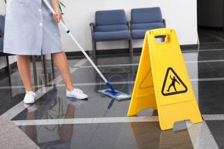 Photo pour Femme de ménage Nettoyage du sol avec de la serpillière dans le bureau - image libre de droit
