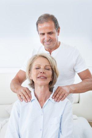 Photo pour Homme mature massant l'épaule de la femme au lit - image libre de droit