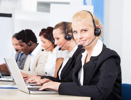 Photo pour Joyeux collègues de travail portant des écouteurs travaillant dans le centre d'appels - image libre de droit