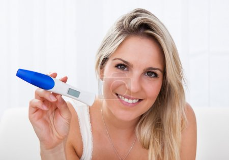 Happy woman looking at positive pregnancy test