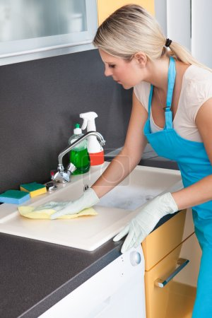 Photo pour Portrait de femme heureuse nettoyage cuisine plan de travail - image libre de droit