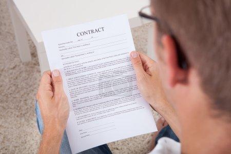 Photo pour Vue aérienne du jeune homme lisant un document contractuel - image libre de droit