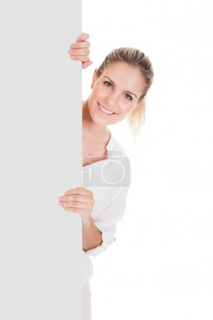 Photo for Young woman standing near blank placard and presenting on white background - Royalty Free Image