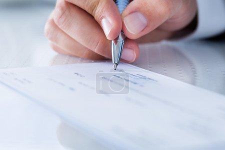 Photo pour Une main masculine remplissant le montant sur un chèque - image libre de droit