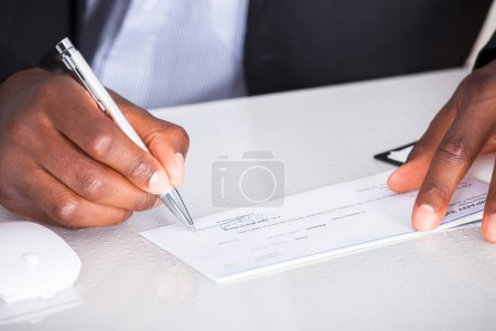 Close-up Of Human Hand Writing On Cheque...
