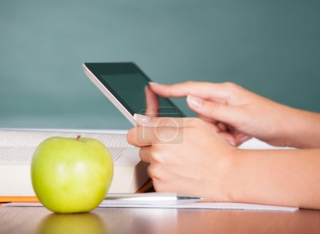 Photo for Student using digital tablet beside green apple while studying - Royalty Free Image